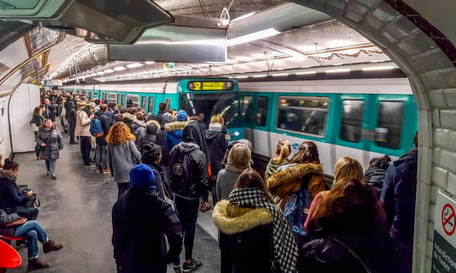 Passengers wait on a Paris metro platform