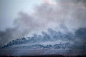 Smoke rises from the Syrian town of Tal Abyad on the second day of Turkey's military operation against Kurdish forces.