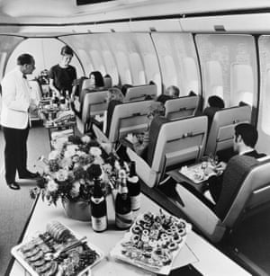 First class passengers in a BOAC Jumbo are served lunch.