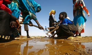 A Sudanese woman fills water bottles held by a young boy about 60km north of El-Fasher, the capital of the North Darfur state, on 9 February 2017.
