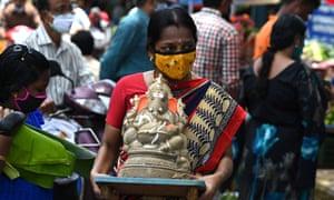 A woman carries an idol of the elephant-headed Hindu god Ganesha through a street during the Ganesh Chaturthi festival in Chennai on September 10, 2021.