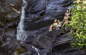 A group of tourists perched on wet, steep rocks.