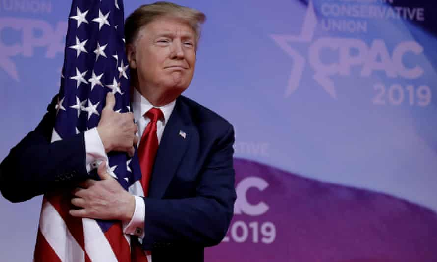 Donald Trump hugs an American flag at CPAC.