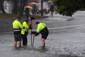 Council workers clear a drain on Railway Terrace in Lewisham during wild weather in Sydney.