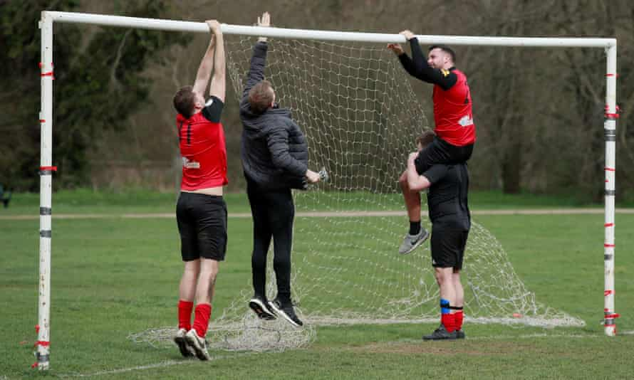 Football players set up goalposts in the park.