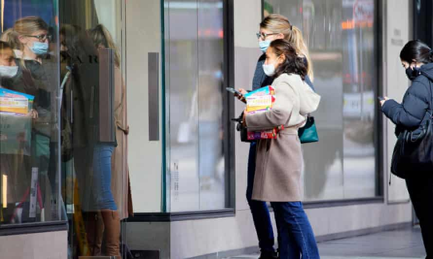 Shoppers wait to enter a store on the first day of eased Covid restrictions in Melbourne, Australia