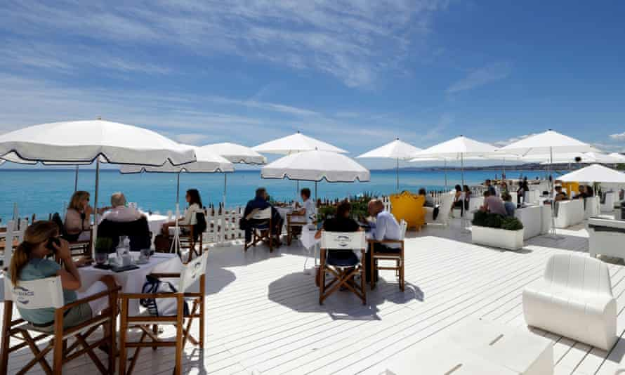 Customers enjoy lunch on the terrace of a beach restaurant in Nice