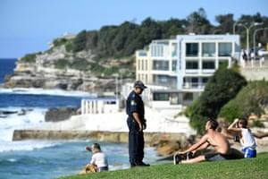 A police officer asks people to move while patrolling during the Easter Long Weekend at Bondi Beach in Sydney, Australia, 12 April 2020.