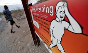 A hiker in Phoenix walks past a heat warning sign at sunrise in July. Arizona's largest city is also and 'urban heat island' – a phenomenon that pushes up temperatures in areas covered in heat-retaining asphalt and concrete.