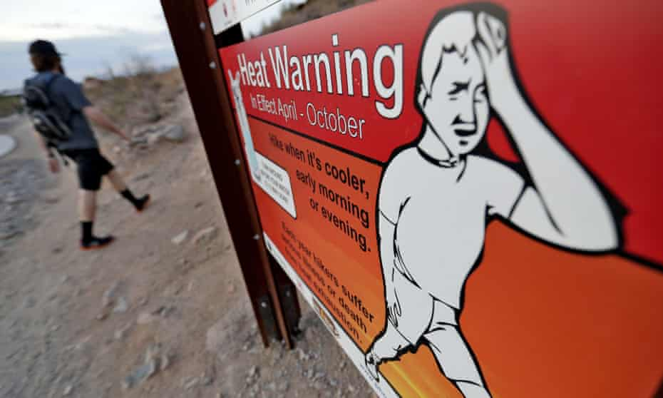 In this Tuesday, July 24, 2018 photo, a hiker walks past a heat warning sign at sunrise, in Phoenix.