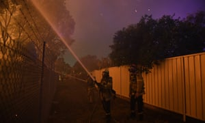 Flames streak closer to homes from a bushfire in Sydney.