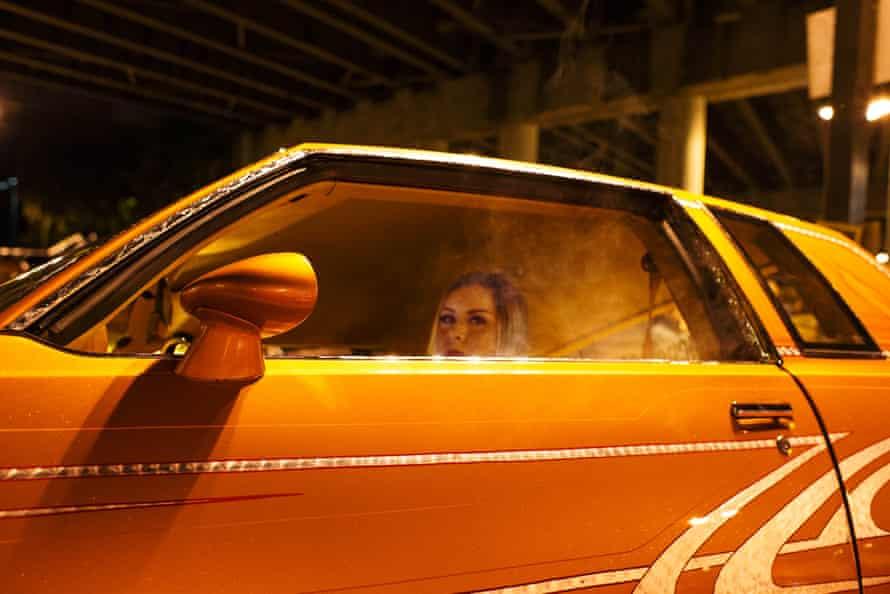woman in driver's seat of orange car