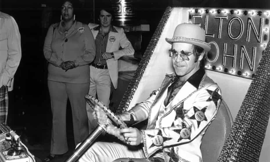 Elton John drives a golf cart to the unveiling of his star on the Hollywood Walk of Fame, 21 October 1975