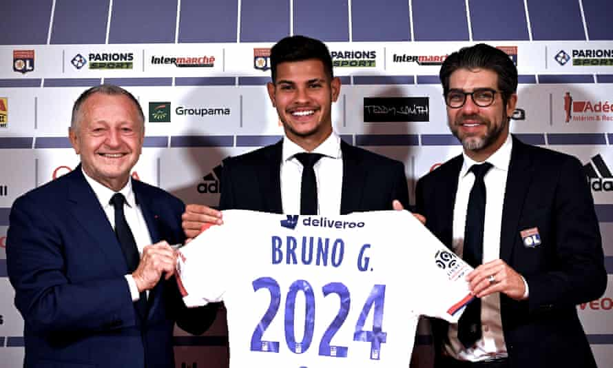 Bruno Guimarães holds the Lyon shirt alongside club president Jean Michel Aulas and director Juninho.