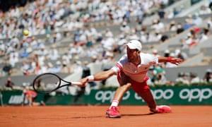 Novak Djokovic stretches for a backhand.