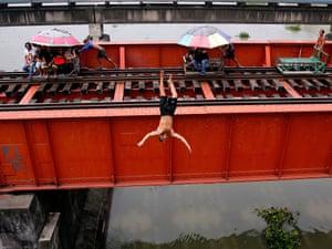 Rickshaws on rails pass by as a man dives from a railway bridge in Manila