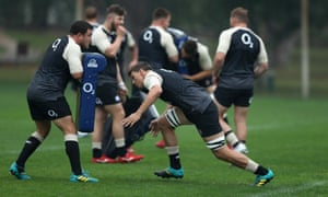 Michael Rhodes charges into a tackle bag held by team mate Jamie George during an England training session.