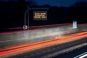 A long exposure photograph of an electronic matrix sign informing motorists on the M6 in Cheshire 'Stay Home Essential Travel Only' in November 2020.