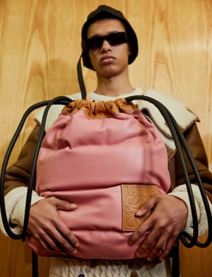 A model backstage at Loewe with a pink drawstring bag.