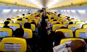 The inside of an aeroplane, showing rows of the backs of heads of passengers