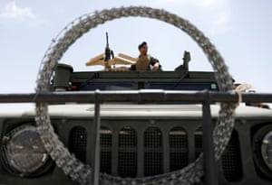 An Afghan security forces member keeps from an army vehicle.