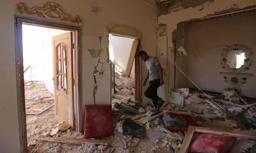 A Syrian man inspects his damaged home in the village of Balyun.