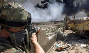 A soldier serving with The Irish Guards looks for possible Iraqi enemy positions on the outskirts of Basra in 2003.