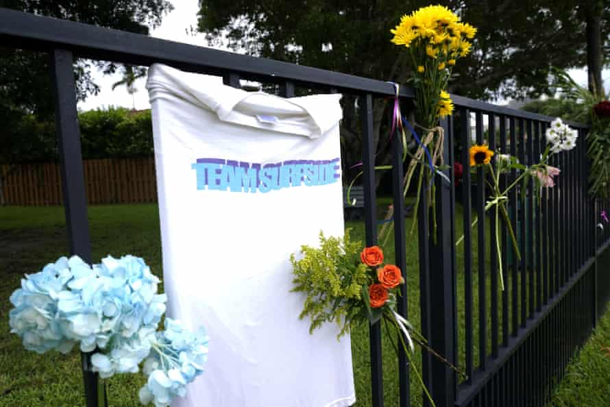 Flowers line a fence near the collapsed building.