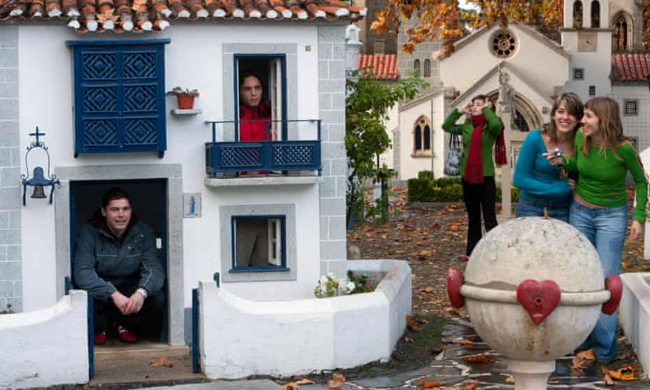 Visitors look at, and hide in, miniature white houses that are part of the Portuguese theme park and attraction Portugal do Pequenitos in Coimbra, Portugal.