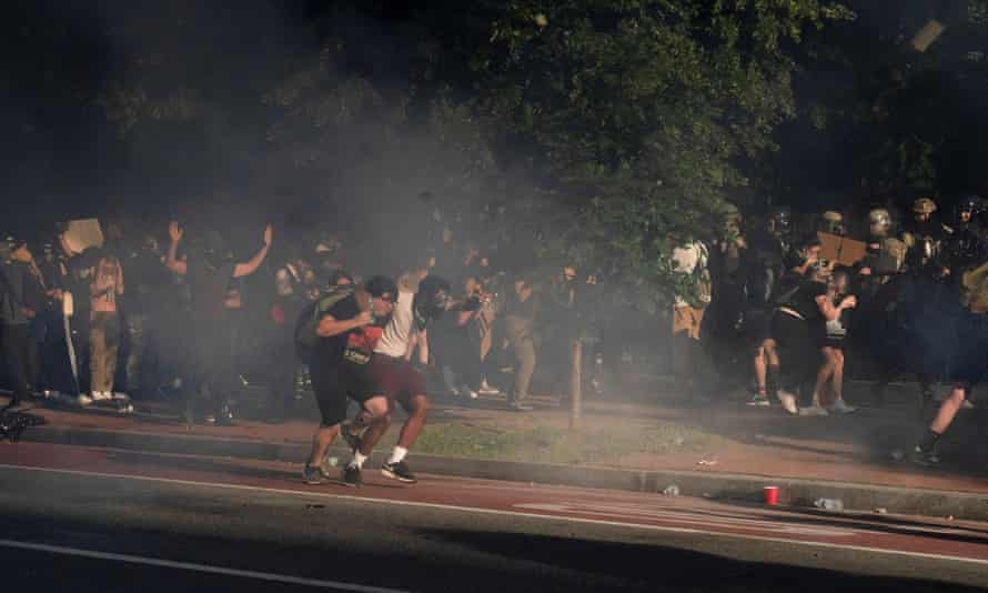 Protestors run as riot police fire teargas to clear Lafayette Park for Donald Trump to be able to walk through for a photo opportunity.