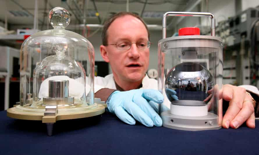 Arnold Nicolaus, of the Physical-Technical Federal Agency, shows a silicon ball next to a copy of the kilogram prototype in Brunswick, Germany.