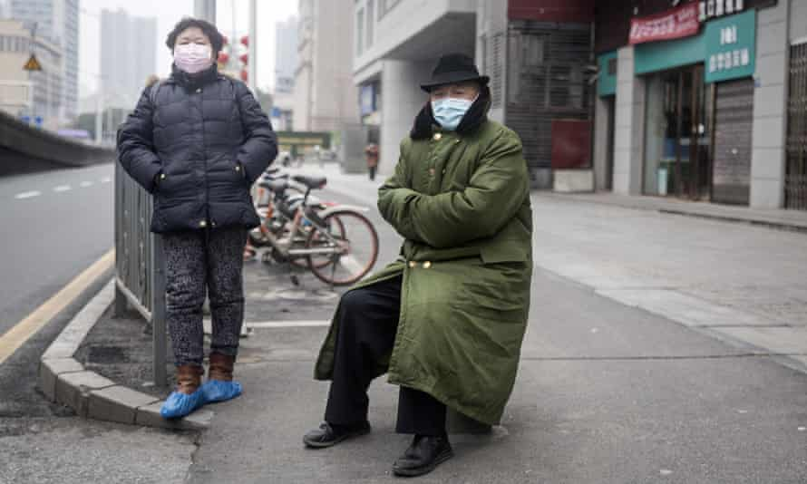 Two residents wearing protective masks on 27 January in Wuhan, China