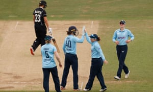 New Zealand's Suzie Bates walks as England's Tammy Beaumont celebrates with teammates after taking a catch to dismiss her.