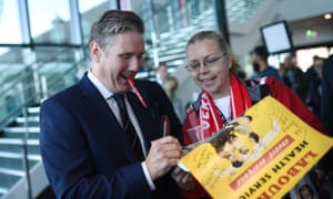 Keir Starmer signing a poster for a delegate at the Labour conference in September.