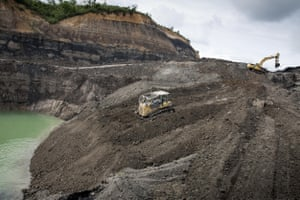 A worker operates an excavator at an open pit-coal mine in Samboja, East Kalimantan, Indonesian Borneo
