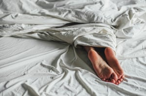 Shot of lfeet of a woman lying in the bed
