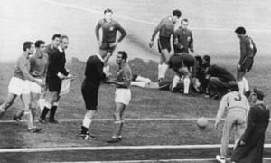 Ken Aston sends off Italy's Mario David, while an injured Chilean player lies on the ground.