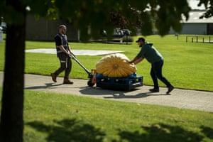 Richard Mann helps a member of show staff manoeuvre his pumpkin on a pallet truck