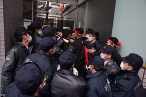 Mob of police officers surround man