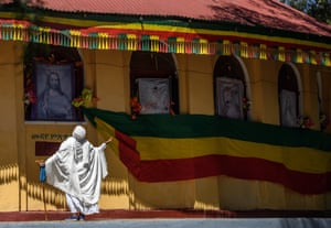 A woman prays next to a large Ethiopian flag and a picture of Christ outside a church