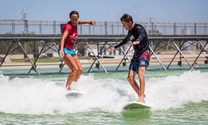 Surfer and instructor ride a wave at NLand Surf Park, Austin Texas