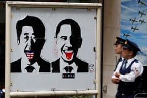Police officers walk past a poster of Japanese prime minister Shinzō Abe and US president Barack Obama as they patrol in Tokyo's Shibuya shopping district