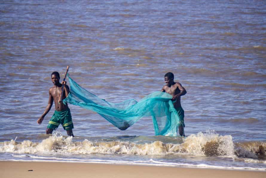 Jose Ferdinand and friend return from a fishing trip in Mozambique's coastal city of Beira