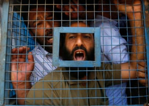 Traders shout from a police vehicle after they were detained during a protest a goods and services tax in Srinagar, India