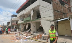 A policeman stands by as a Venezuelan rescue team tries to recover the body of María Victoria Chávez from the rubble of a four-storey building.
