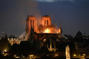 Firefighters douse flames rising from the roof at Notre-Dame Cathedral in Paris.