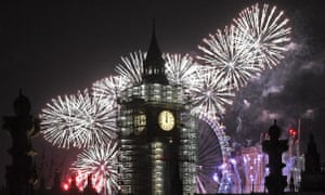 Fireworks explode over Big Ben and the giant Ferris wheel of the London Eye at midnight in London.