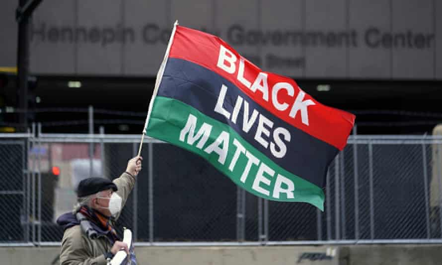 A protesters waves a Black Lives Matter flag across the street from the Hennepin county government center in Minneapolis where testimony continues in the trial of Derek Chauvin.