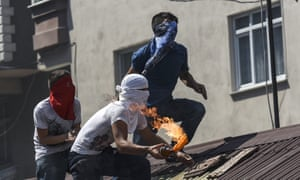 Protesters prepare to throw a Molotov cocktail from a rooftop during clashes with Turkish police in Istanbul on Sunday.