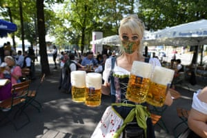 A server carries mugs during a barrel tapping at a beer garden near Theresienwiese in Munich, Germany on 19 September, 2020, where Oktoberfest would have started today had it not been cancelled due to the pandemic.